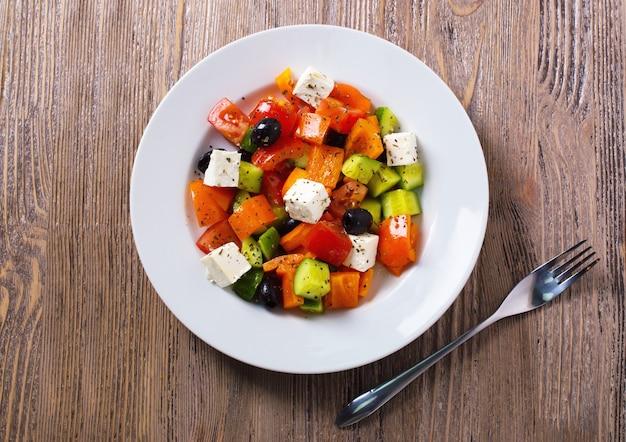 Salada grega de pepino fresco, tomate, pimento doce, queijo feta e azeitonas com azeite e especiarias. comida saudável, vista de cima