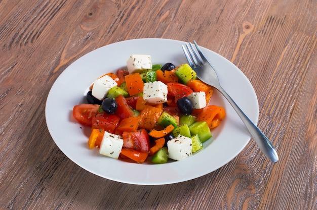 Salada grega de pepino fresco, tomate, pimento doce, queijo feta e azeitonas com azeite e especiarias. comida saudável