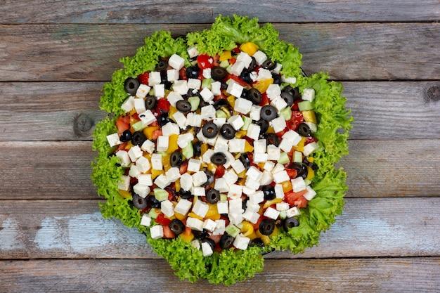 Salada grega de pepinos frescos, tomates, pimentões, queijo feta e azeitonas com azeite emoldurada por folhas verdes de alface em uma mesa de madeira, vista de cima close-up