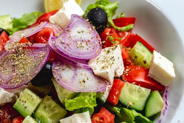 Salada grega de vista lateral com queijo branco cebola vermelha azeitona preta tomate pepino alface orégano e azeite