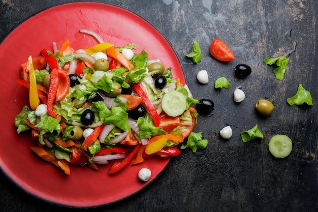 Salada grega de vista superior com tomate e azeitona e queijo feta no prato vermelho