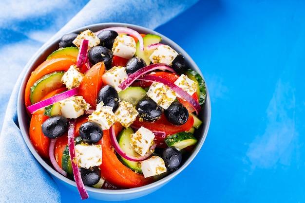Salada grega e guardanapo azul sobre um fundo azul. legumes frescos, queijo feta e azeitonas pretas. cozinha grega. vista do topo. copie o espaço