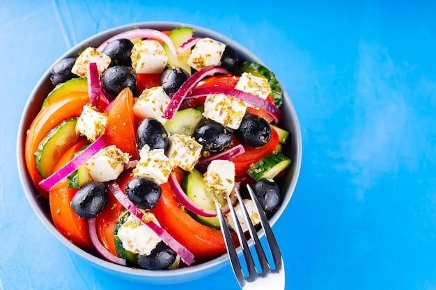Salada grega e um garfo sobre um fundo azul. legumes frescos, queijo feta e azeitonas pretas. comida da moda. copie o espaço. vista do topo