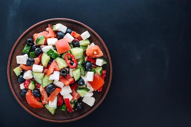 Salada grega em um prato no escuro