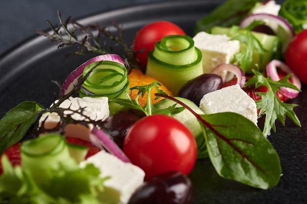 Salada grega fresca com tomate, pepino, pimentão, azeitonas e queijo feta na chapa preta, macro, foco seletivo, estilo de comida
