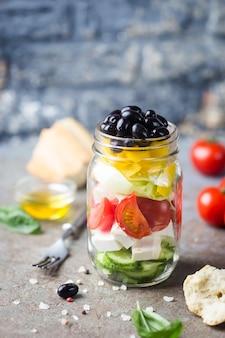 Salada grega fresca de pepino, tomate, pimentão, queijo feta e azeitonas com azeite em uma jarra de vidro
