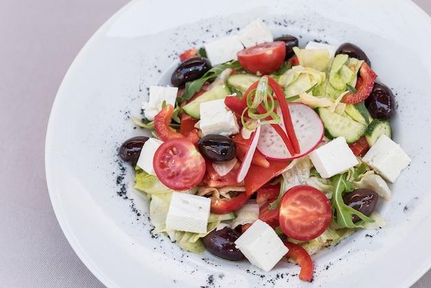 Salada grega fresca, decorada com ervas, isolado no fundo claro, placa branca