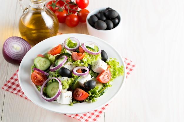 Salada grega fresca feita do tomate de cereja, do ruccola, da rúcula, do feta, das azeitonas, dos pepinos, da cebola e das especiarias.