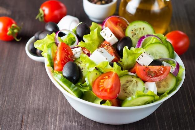 Salada grega fresca no fundo de madeira.