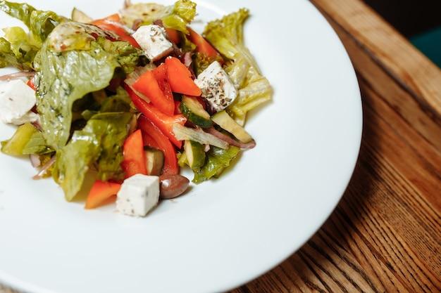 Salada grega na vista superior do fundo de madeira. espaço para texto. comida saudável.