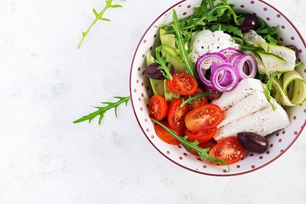 Salada grega saudável de pepino fresco, tomate, abacate, rúcula, cebola roxa, queijo feta e azeitonas