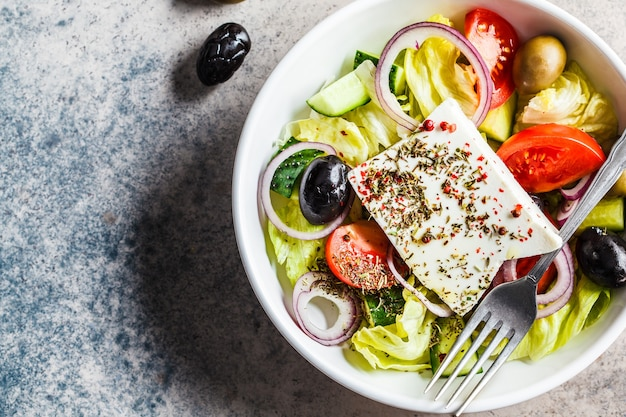 Salada grega tradicional com queijo feta, azeitonas, tomate e pepino em prato branco, vista de cima.