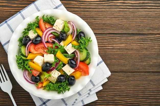 Salada grega tradicional de pepino fresco, tomate, pimentão, alface, cebola roxa, queijo feta e azeitonas com azeite no prato branco. alimentação saudável, vista superior.