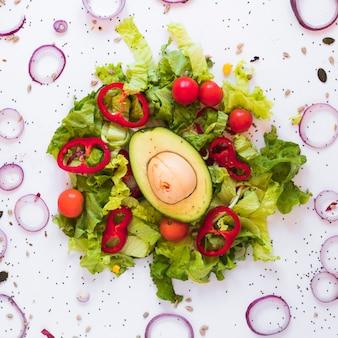 Salada guarnecida saudável contra isolado no fundo branco