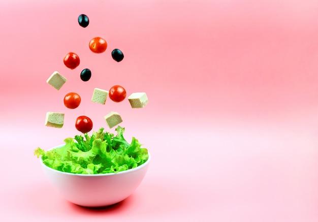 Salada ingredientes tomate cereja, azeitonas, queijo tofu caindo no arco