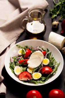 Salada italiana preparada com rúcula, mussarela, ovos. feche acima do tiro