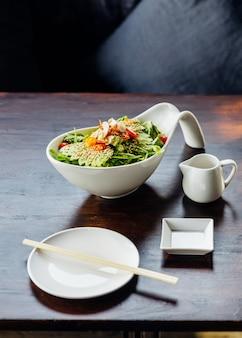 Salada japonesa com abacate, tomate, carvalho verde, amêndoa e gergelim.