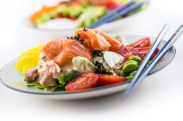 Salada japonesa com peixe, salmão e vegetais e pauzinhos.