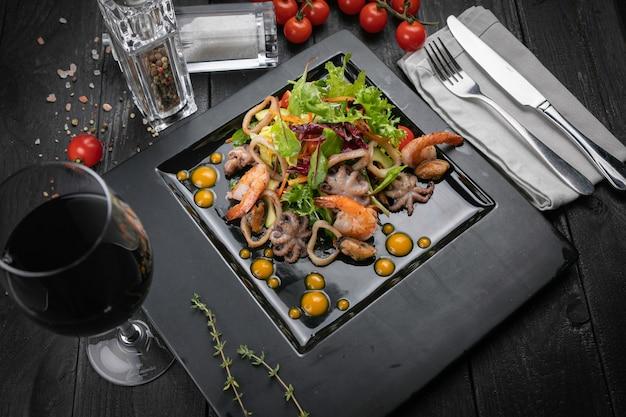 Salada japonesa de frutos do mar em um prato preto e fundo de madeira