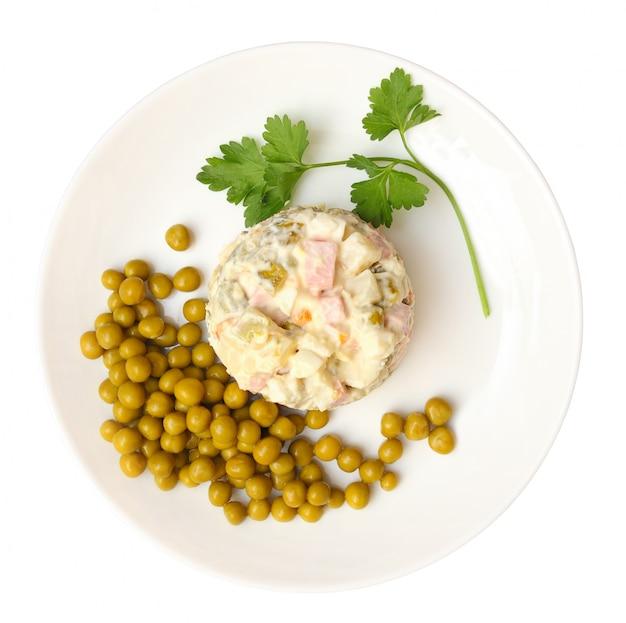 Salada mais olivier, ervilhas verdes em um prato isolado no fundo branco com traçado de recorte. vista do topo.