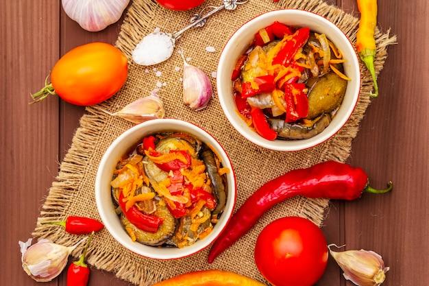 Salada marinada com legumes em conserva: berinjela, cenoura, pimenta, tomate, alho