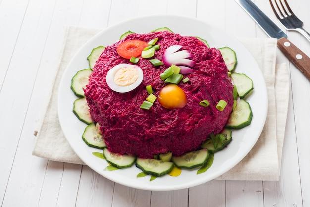 Salada mergulhada com arenques e beterrabas, cenouras e batatas e close-up dos ovos em uma placa.