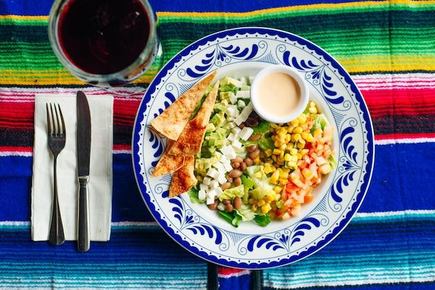 Salada mexicana com milho, pimenta, batata frita, queijo, abacate e molho.