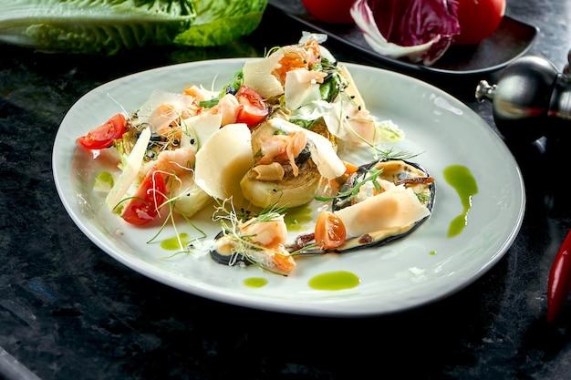 Salada mista com camarão grelhado, parmesão e alcachofra servida em prato branco sobre mesa de mármore escuro. comida do restaurante.