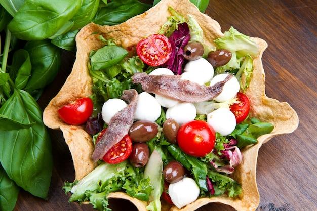 Salada mista com mussarela e anchova em uma cesta de pão