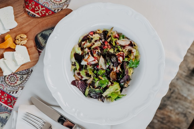Salada mista de legumes verdes com vinagre balsâmico dentro da placa branca.