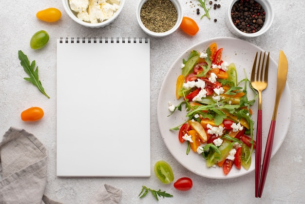 Salada mista de tomate com queijo feta, rúcula e caderno em branco