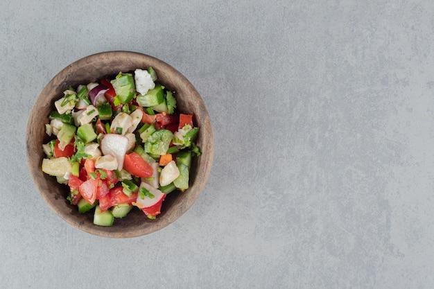 Salada mista de vegetais em um copo de madeira na mesa de concreto.