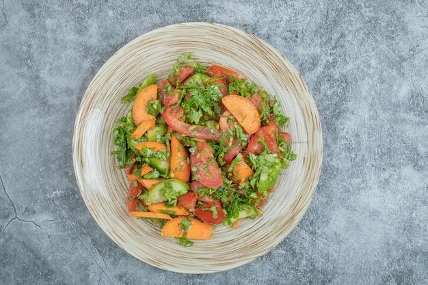 Salada mista de vegetais no prato de cerâmica.
