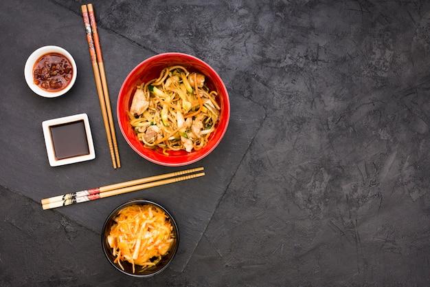Salada; molhos e macarrão servido na tigela com pauzinhos