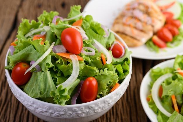 Salada na tigela na mesa de madeira.