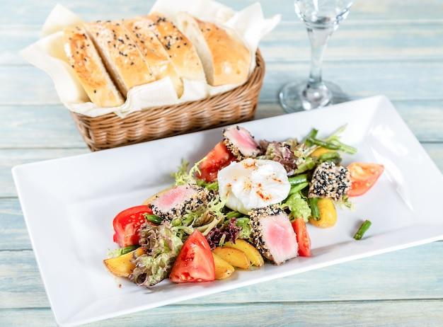 Salada nicoise com atum assado e ovo escalfado na mesa de madeira
