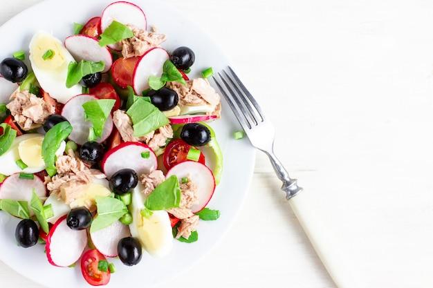 Salada nicoise com atum, ovo, tomate cereja e azeitonas pretas. cozinha francesa. vista do topo