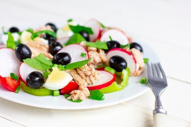 Salada nicoise com atum, ovo, tomate cereja e azeitonas pretas. cozinha francesa