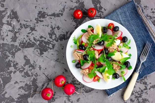 Salada nicoise com atum, ovo, tomate cereja e azeitonas pretas sobre fundo cinza escuro