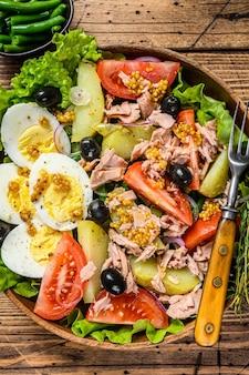 Salada nicoise com atum, tomate, azeitonas, vagem, pepino, ovos cozidos e batata numa tigela de madeira. mesa de madeira. vista do topo.