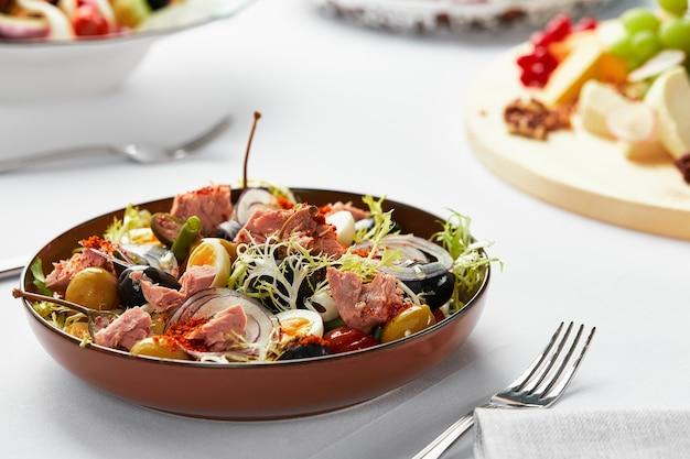 Salada nicoise na mesa de banquete, clássica salada nicoise servida pelo chef em prato artesanal, salada de atum com ovos e azeitonas.