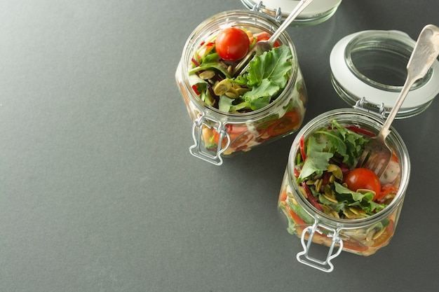Salada no frasco de vidro com legumes frescos, ervilha de pintainho e sementes de abóbora. copie o espaço.