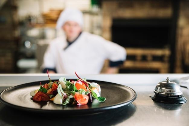 Salada no prato com sino de serviço