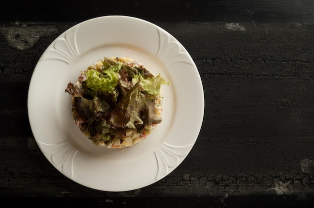Salada olivier em um prato branco sobre uma superfície de madeira velha salada olivier com verduras em um prato redondo