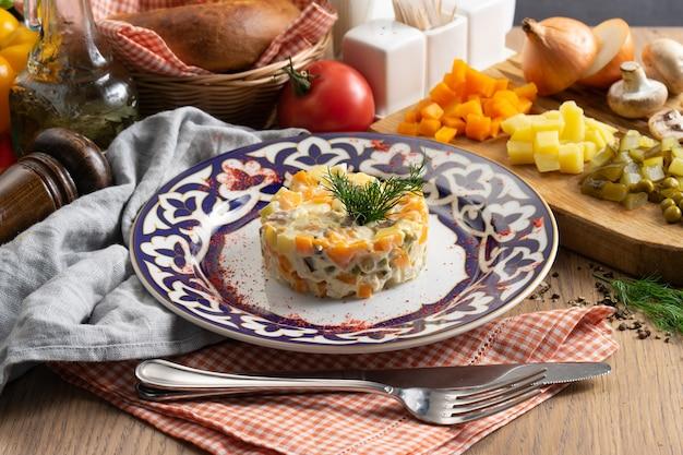 Salada olivier - uma salada russa tradicional de vegetais, salsicha e maionese em um prato com um uzbeque tradicional