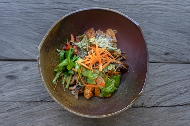 Salada orgânica de arroz com curry verde, berinjela, kimchi, verdes refogados, cogumelos, bacon de tempeh, tofu é servida em uma tigela de barro. fechar-se. o conceito de alimentação saudável.