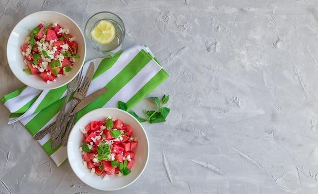 Salada orgânica fresca com melancia, queijo feta e hortelã em fundo de concreto cinza claro. comida vegetariana saudável. vista do topo. copie a área do espaço.