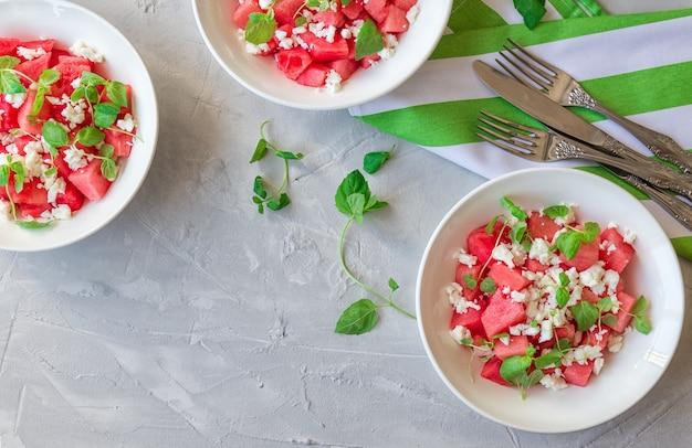 Salada orgânica fresca com melancia, queijo feta e hortelã em tigelas na superfície de concreto cinza claro. comida vegetariana saudável. vista do topo.