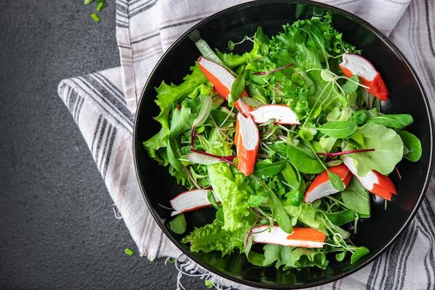 Salada palito de caranguejo folhas de alface verde misture pétalas porção fresca refeição lanche na mesa copie espaço