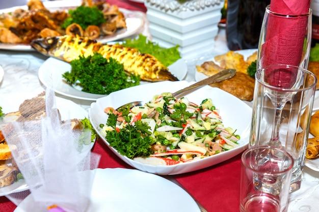 Salada, peixe e outros pratos na mesa do banquete